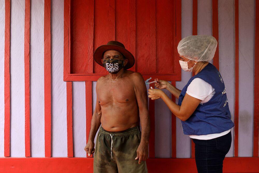 Municipal health worker Ana Cassia Oliveira de Lima administers an AstraZeneca coronavirus disease (COVID-19) vaccine to Joao Aquino Filho, 75, during a vaccination day along the Rio Negro banks.