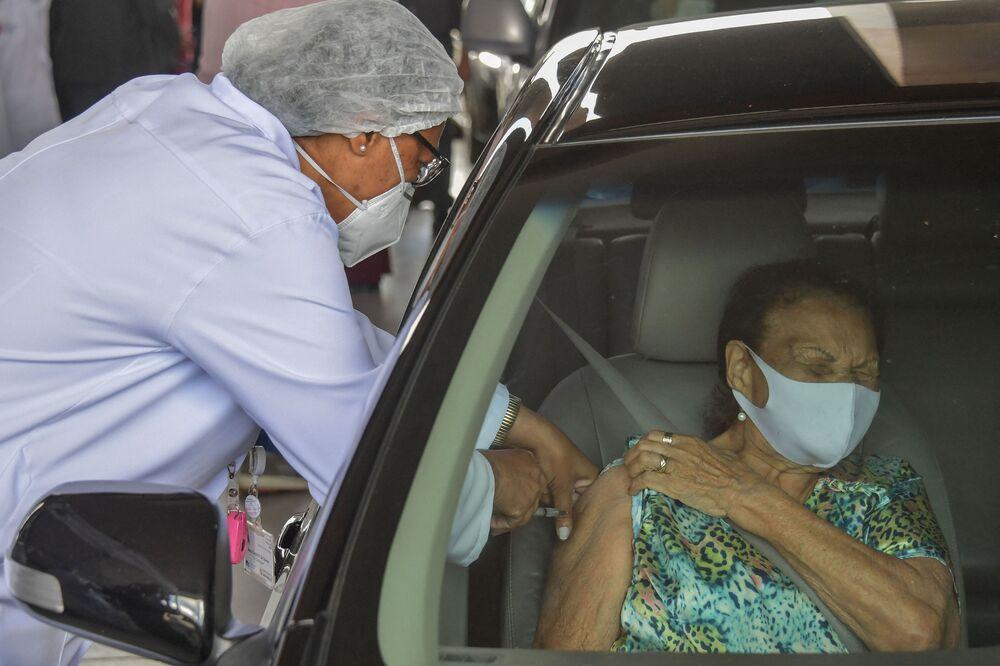 An elderly Brazilian woman receives a dose of the Coronavac vaccine at a drive-through vaccination centre at the Pacaembu Stadium in Sao Paulo, Brazil.