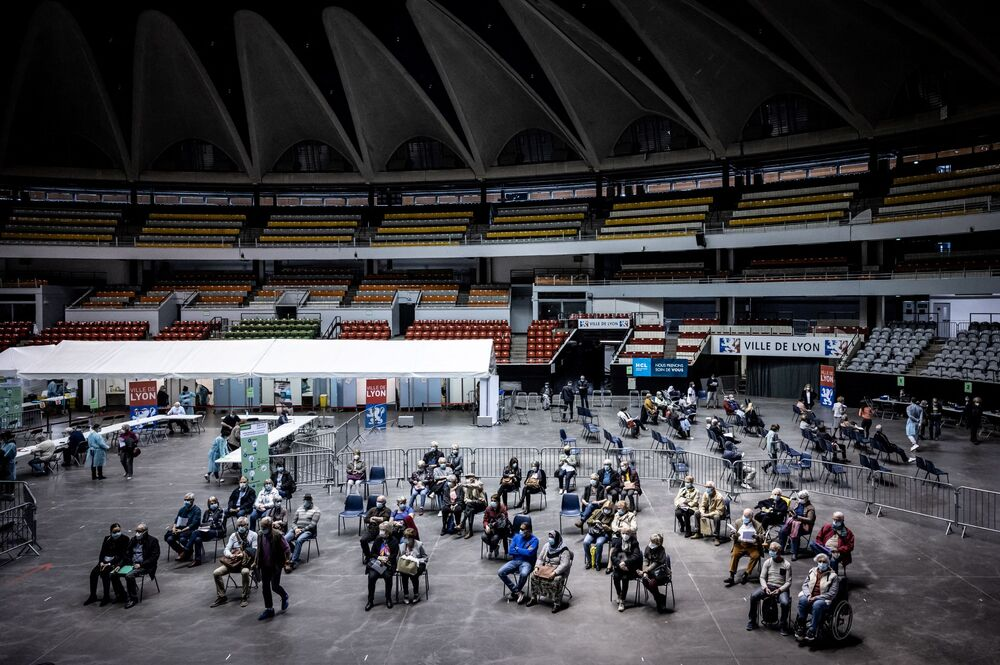 People arrive and wait at the Palais des Sports venue in Lyon, hosting a COVID-19 vaccination centre.