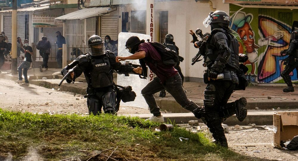 Riot police detain a demonstrator during a protest against sexual assault by the police and the excess of public force against peaceful protests, in Popayan, Colombia 14 May 2021.