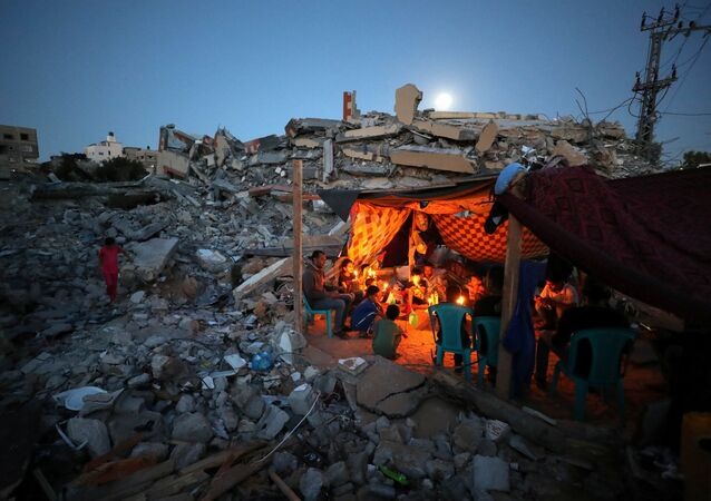 Palestinians from Zawaraa family hold candles as they sit in a makeshift tent amid the rubble of their houses which were destroyed by Israeli air strikes during the Israeli-Palestinian fighting in Gaza May 25, 2021.