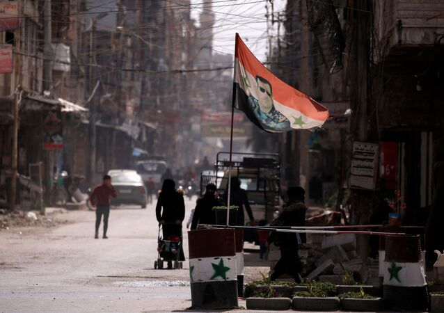 A national flag depicting a picture of Syria's President Bashar al-Assad flutters at a checkpoint in Douma, in the eastern suburbs of Damascus, Syria March 10, 2021. Picture taken March 10, 2021.