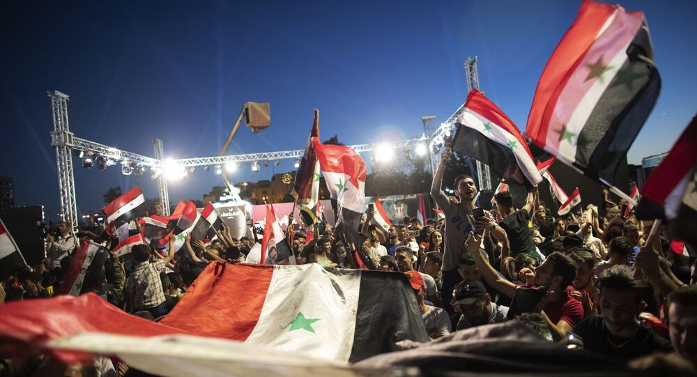 Syrian President Bashar Assad supporters hold up national flags and pictures of Assad as they celebrate at Omayyad Square, in Damascus, Syria, Thursday, May 27, 2021.