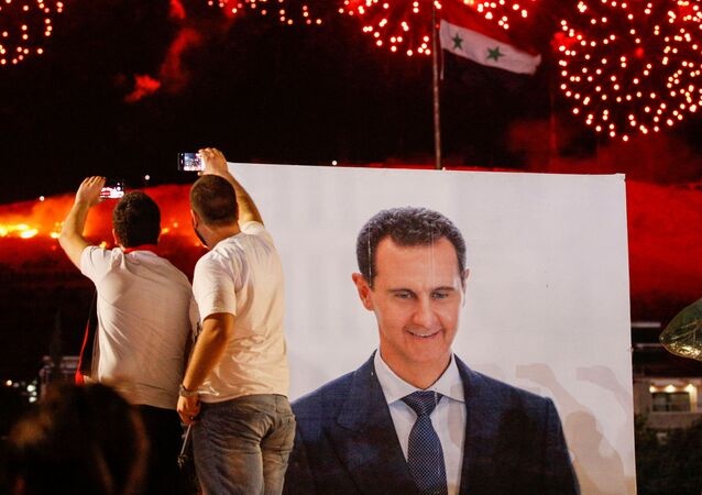 A poster depicting Syria's president Bashar al- Assad is seen as supporters of of Syria's President Bashar al-Assad celebrate after the results of the presidential election announced that he won a fourth term in office, in Damascus, Syria, May 27, 2021.