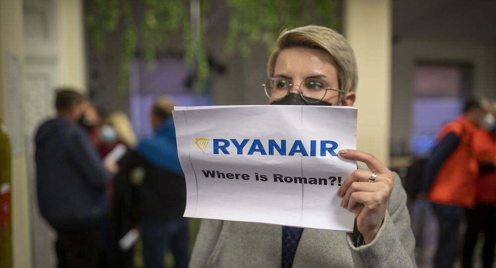 A woman holds a poster reads where is Roman?! as she waits to see passengers of the Ryanair plane with registration number SP-RSM, carrying opposition figure Roman Protasevich which was traveling from Athens to Vilnius and was diverted to Minsk after a bomb threat, after its landing at the International Airport outside Vilnius, Lithuania, Sunday, May 23, 2021