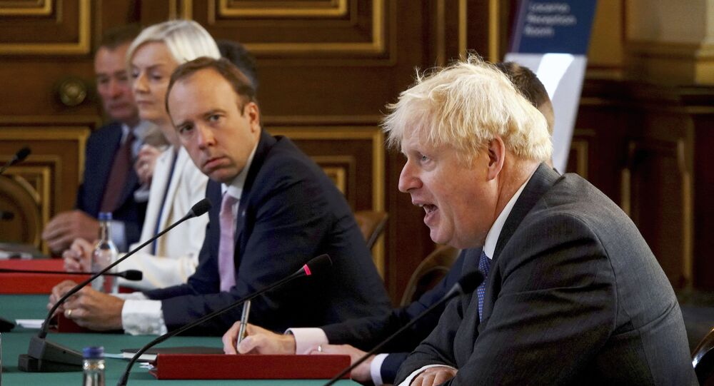 Britain's Prime Minister Boris Johnson, right, chairs a socially distanced government Cabinet meeting at the Foreign and Commonwealth Office (FCO) in London, Tuesday Sept. 15, 2020.