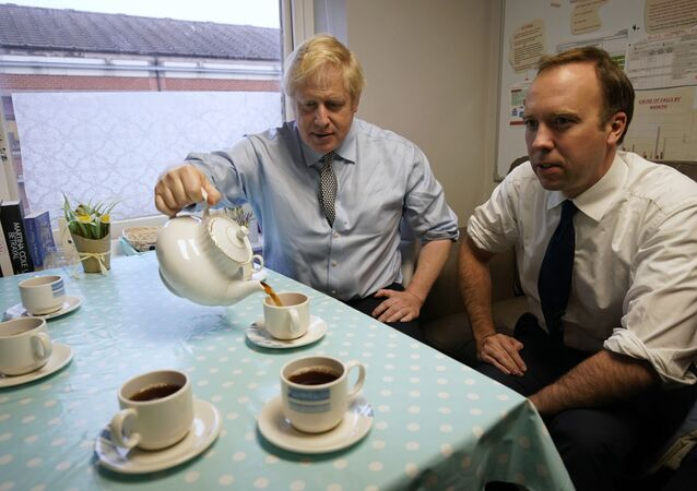 Secretary of State for Health and Social Care Matt Hancock, right, and Prime Minister Boris Johnson have tea with members of staff as they visit Bassetlaw District General Hospital, during their General Election campaign in Worksop, England, Friday, Nov. 22, 2019.
