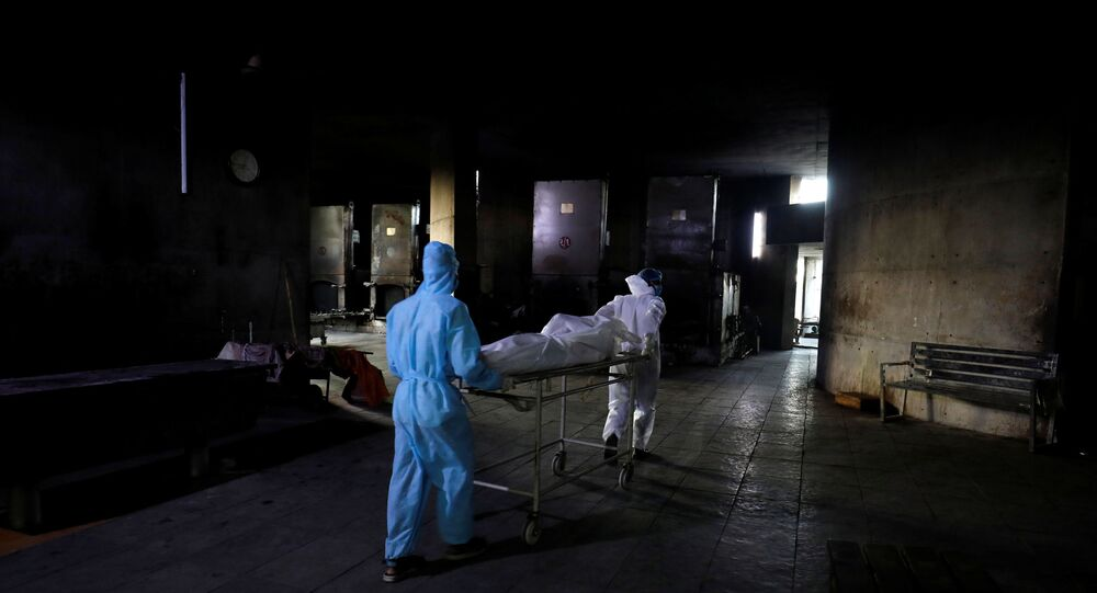 SENSITIVE MATERIAL. THIS IMAGE MAY OFFEND OR DISTURB    Workers move the body of a person who died from the coronavirus disease (COVID-19) for cremation inside the Kurukshetra crematorium in Surat, India, May 11, 2021.