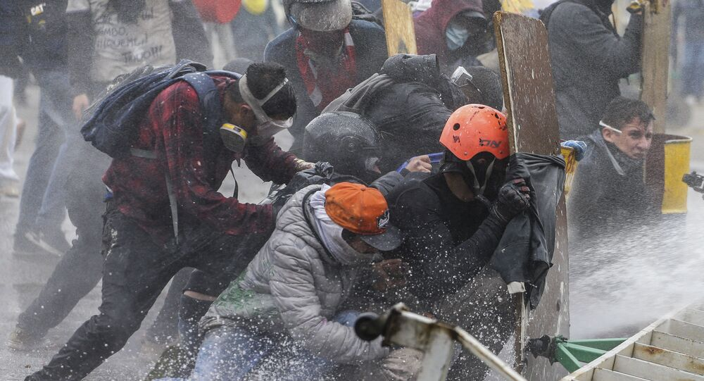 Anti-government protesters take cover from a police water cannon during clashes in Madrid, on the outskirts of Bogota, Colombia, Friday, May 28, 2021.
