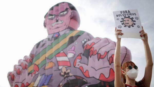 A demonstrator holds a banner reading Bolsonaro virus out during a protest against Brazil's President Jair Bolsonaro in Brasilia, Brazil, May 29, 2021. - Sputnik International