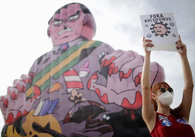 A demonstrator holds a banner reading Bolsonaro virus out during a protest against Brazil's President Jair Bolsonaro in Brasilia, Brazil, May 29, 2021.