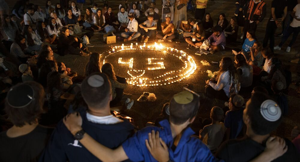 People gather around candles during a vigil in memory of the 45 ultra-Orthodox Jews killed in a stampede at a religious festival in northern Israel on Friday, in Tel Aviv, Israel, Sunday, 2 May 2021.
