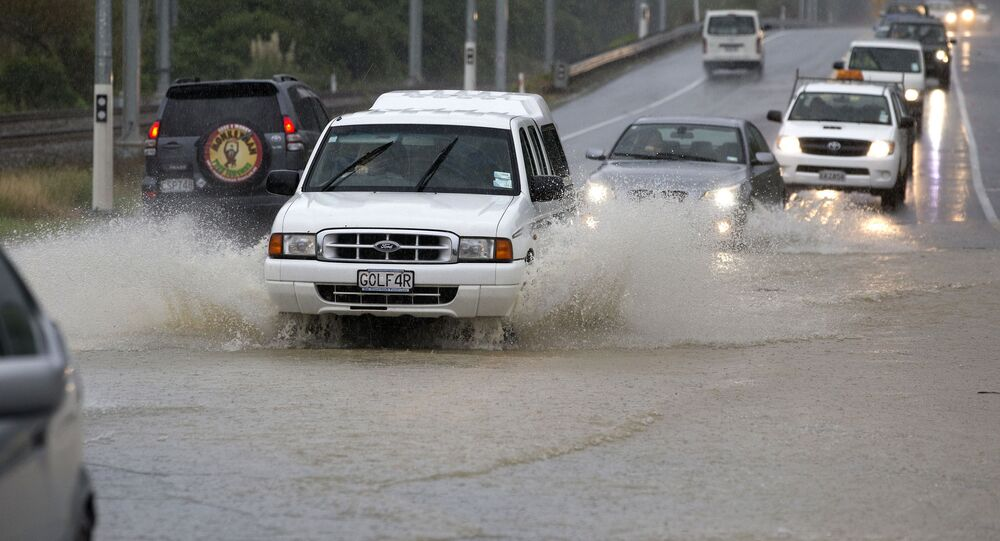 Traffic negotiates a flooded highway north of Wellington on State Highway One, New Zealand, Thursday, May 14, 2015.