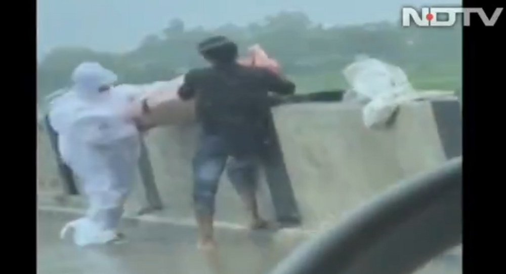 Watch Two Men Dumping COVID Patient's Body Into River in India