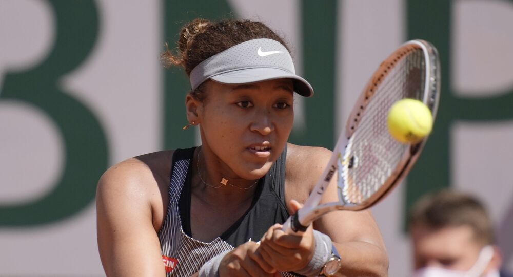 Japan's Naomi Osaka returns the ball to Romania's Patricia Maria Tig during their first round match of the French open tennis tournament at the Roland Garros stadium Sunday, 30 May 2021 in Paris.