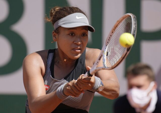 Japan's Naomi Osaka returns the ball to Romania's Patricia Maria Tig during their first round match of the French open tennis tournament at the Roland Garros stadium Sunday, May 30, 2021 in Paris.