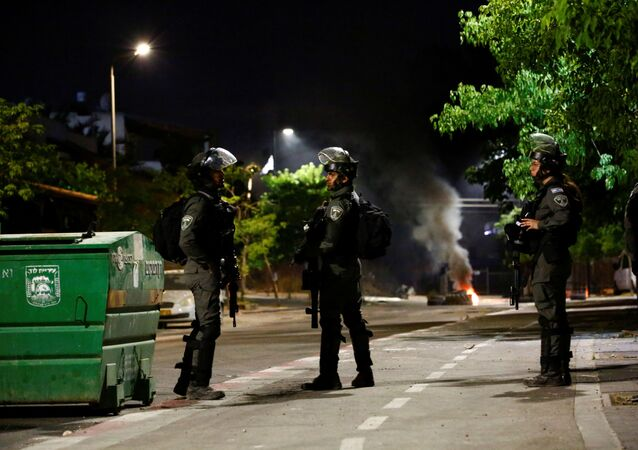 sraeli Border Police force members stand near burning tires by one of the entrances to the Arab-Jewish town of Lod, Israel May 13, 2021