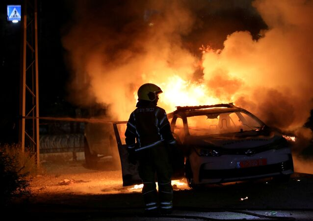 An Israeli firefighter stands near a burning Israeli police car during clashes between Israeli police and members of the country's Arab minority in the Arab-Jewish town of Lod, Israel May 12, 2021