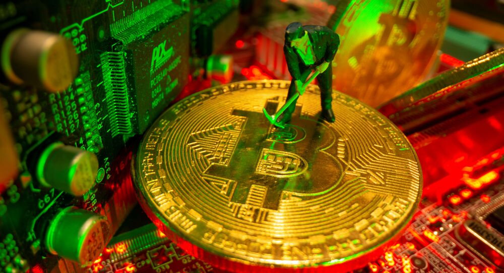 A small toy figure and representations of the virtual currency Bitcoin stand on a motherboard in this picture illustration taken May 20, 2021.