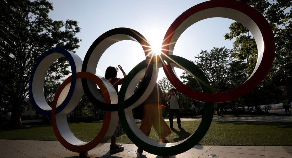 Visitors try to take photos in front of the Olympic Rings monument outside the Japan Olympic Committee (JOC) headquarters near the National Stadium, the main stadium for the 2020 Tokyo Olympic Games that have been postponed to 2021 due to the coronavirus disease (COVID-19) outbreak, in Tokyo, Japan May 30, 2021.