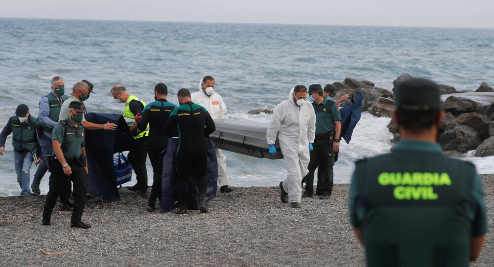 Workers carry a coffin containing a body at the shore near the Spanish-Moroccan border at El Tarajal Beach, after thousands of migrants swam across this border during the last days, in Ceuta, Spain, May 20, 2021