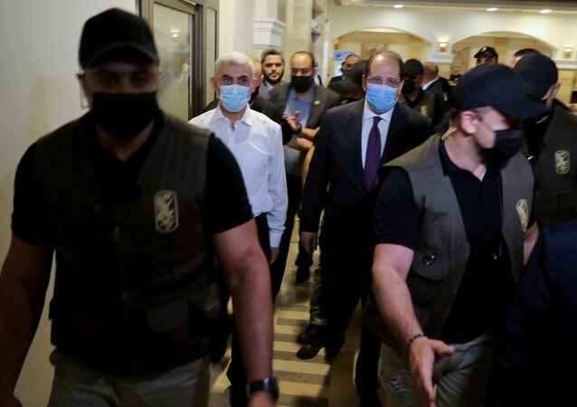 Palestinian Hamas Gaza Chief Yehya Al-Sinwar and head of the Egyptian general intelligence Abbas Kamel walk as they meet in Gaza on 31 May 2021.