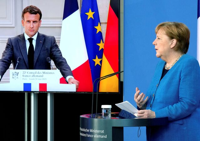French President Emmanuel Macron is seen on a video screen during a joint press conference with German Chancellor Angela Merkel, as part of a virtual Plenary Session of the Franco-German Council of Ministers in Berlin, Germany, May 31, 2021.