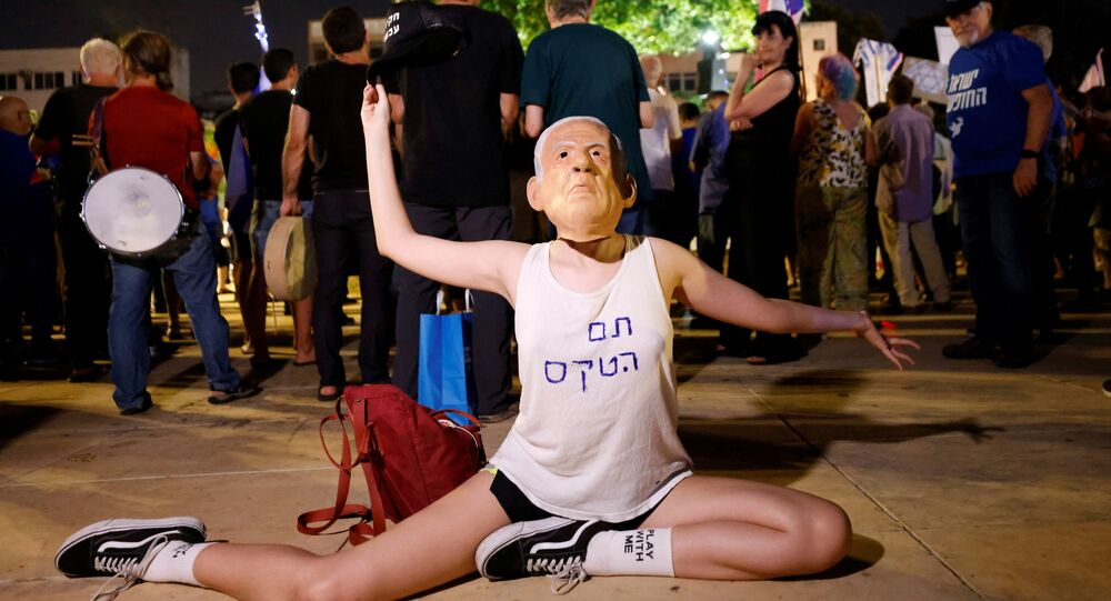 A protester wearing a mask of Prime Minister Benjamin Netanyahu and a t-shirt reading Ceremony is over gestures during a rally in support of a so-called government of change, a day after far-right party leader Naftali Bennett threw his crucial support behind a unity government in Israel to unseat Netanyahu, in Tel Aviv, Israel May 31, 2021