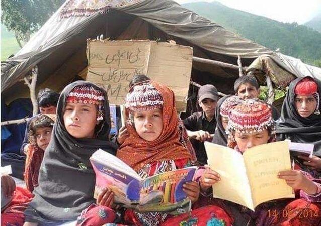 Gujjar's children attending temporary classes outside their makeshift tent in Zhampatri, Shopian