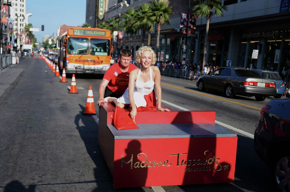 A worker of Madame Tussauds Museum in Hollywood pushes a wax figurine of Marilyn Monroe along Hollywood Boulevard in California.