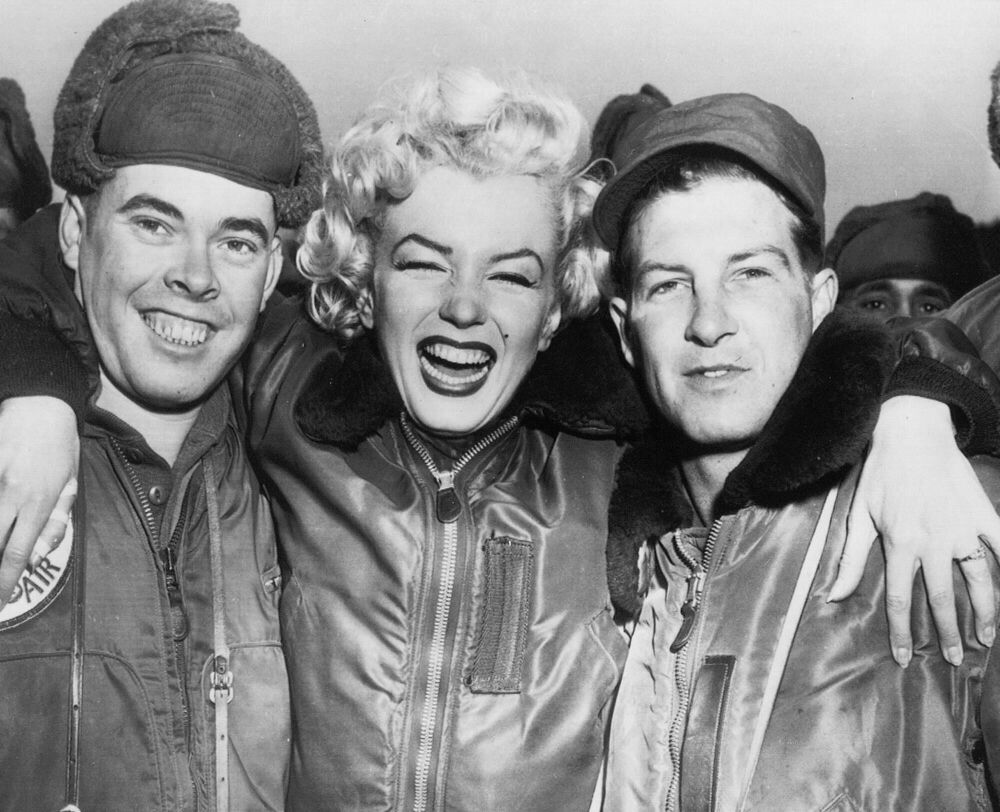 Marilyn Monroe puts her arms around Pfc. John Fenesy, left, of Caldwell, New Jersey and Cpl. Dick Armstrong, right, of Williston Park, New York, at the 3rd division airstrip during her four-day tour of Korea, 19 February 1954.