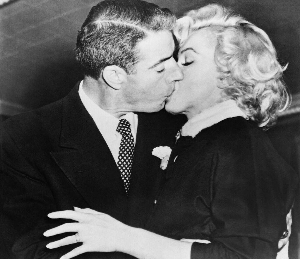 American actress Marilyn Monroe kisses her husband, former baseball player Joe Di Maggio, on 14 January 1954.
