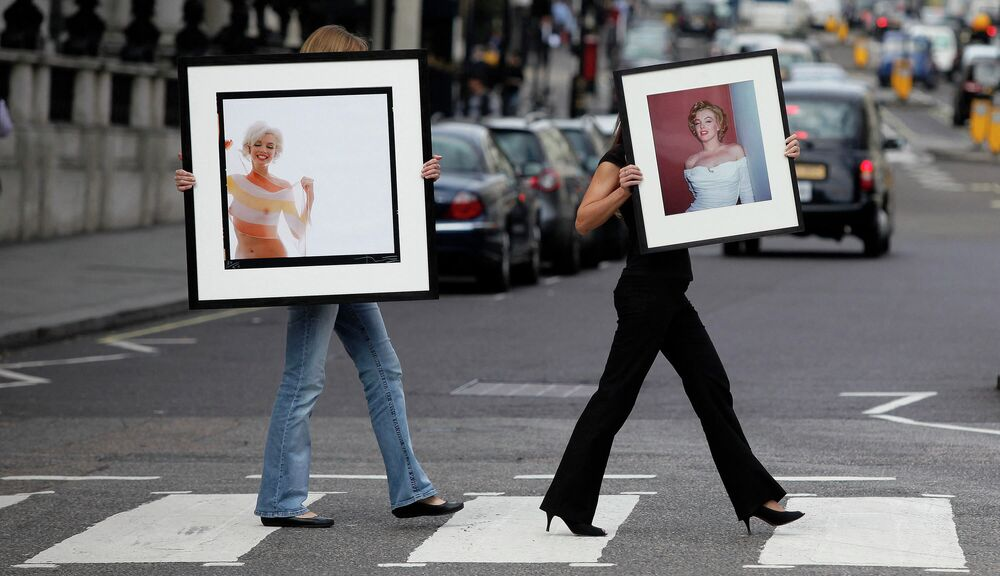 Lyon and Turnbull employees pose with two of the last photographs taken of Marilyn Monroe: 'Marilyn Monroe in Stripe Scarf (The Last Sitting)' (L) by Bert Stern and 'Marilyn Monroe with white cocktail dress' (R) by Harold Lloyd during a photocall in central London.
