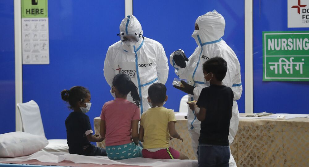Doctors and health workers keep children amused at a COVID-19 care centre built in an indoor stadium in New Delhi, India on Monday, 20 July 2020.