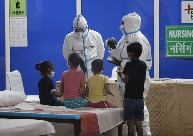 Doctors and health workers entertain children at a COVID-19 care center built in an indoor stadium in New Delhi, India, Monday, 20 July 2020