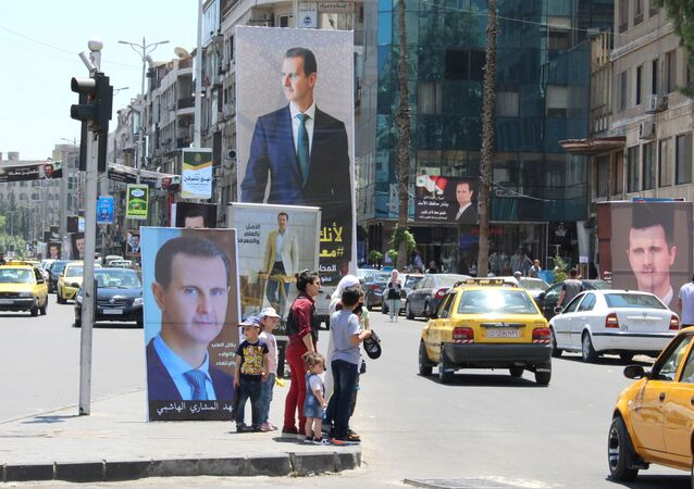 People stand near posters depicting Syria's President Bashar al-Assad, ahead of the May 26 presidential election, in Damascus, Syria May 18, 2021