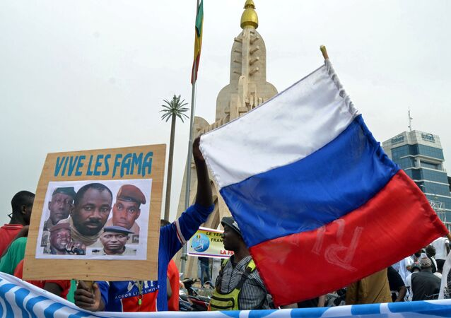 Malians holds a photograph with an image of coup leader Colonel Assimi Goita, who overthrew the president and prime minister this week, and Russia's flag during a pro-Malian Armed Forces (FAMA)  demonstration in Bamako, Mali, May 28, 2021