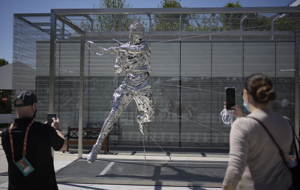 Spectators take photos of a new statue of Spain's Rafael Nadal on day two of the French Open tennis tournament at Stade Roland-Garros in Paris, France on Monday 31 May 2021.