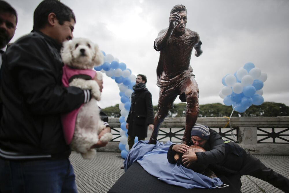 A man kisses a statue of soccer star Lionel Messi shortly after its unveiling in Buenos Aires, Argentina on Tuesday 28 June 2016. Fans, players, Argentina's President Mauricio Macri and the country's greatest player Diego Maradona have asked the Argentine Messi to reconsider his decision to resign from the national team after losing the Copa America final to Chile.
