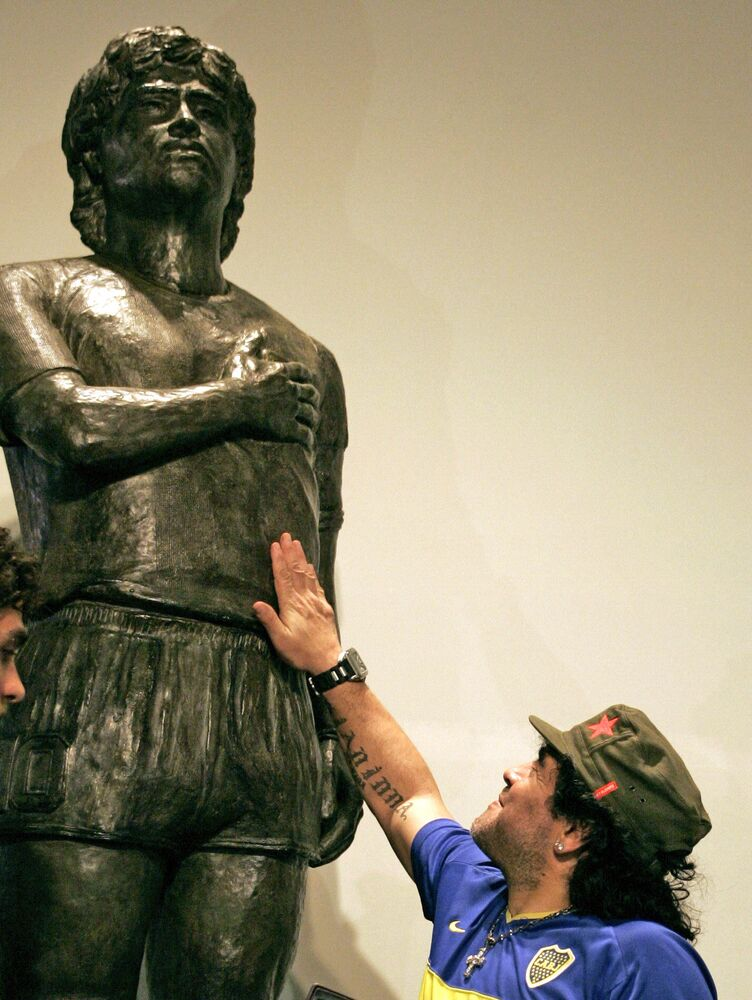 Former soccer star Diego Maradona poses in front of his statue, commissioned as a tribute by a group of fans, at the Boca Juniors Museum (Museo de la Pasion Boquense), in La Bombonera stadium, Buenos Aires on 26 November 2006. The 2.2-metres statue weighs 300kg.