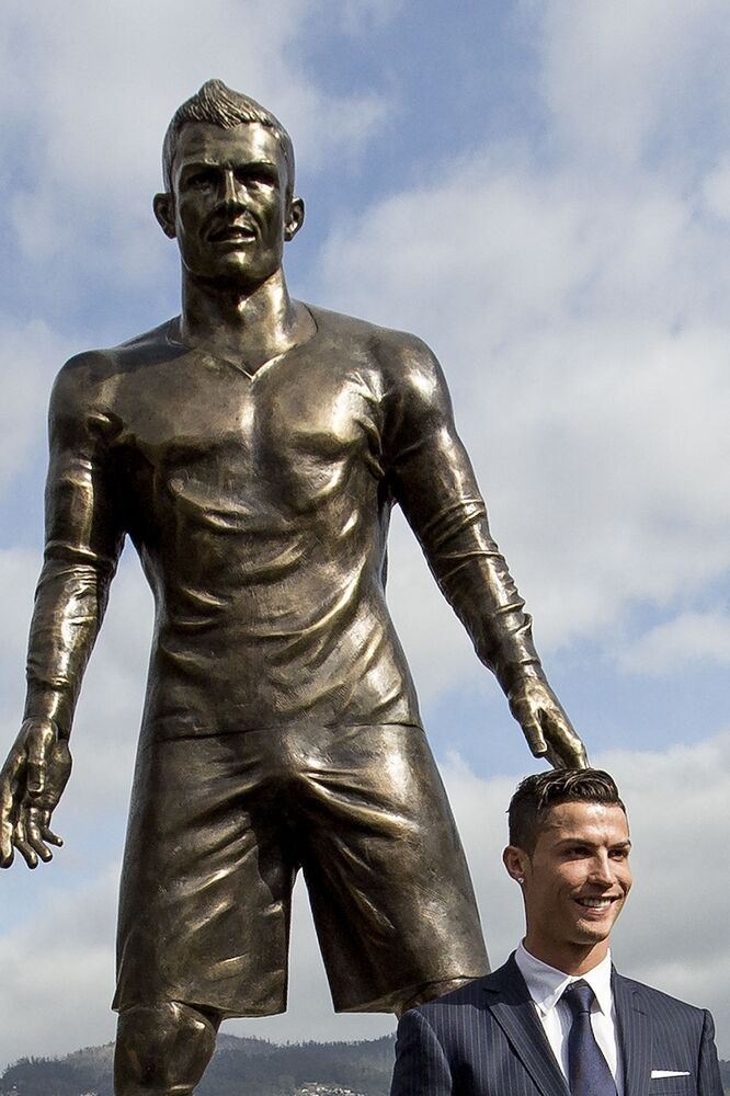 Portuguese football player Cristiano Ronaldo from Real Madrid poses beneath a statue of himself during the unveiling ceremony in his hometown in Funchal, Portugal on 21 December 2014.