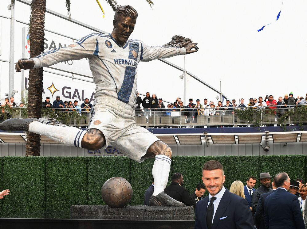 Former Los Angeles Galaxy midfielder David Beckham poses beside his newly unveiled statue at the Legends Plaza in Carson, California on 2 March 2019.
