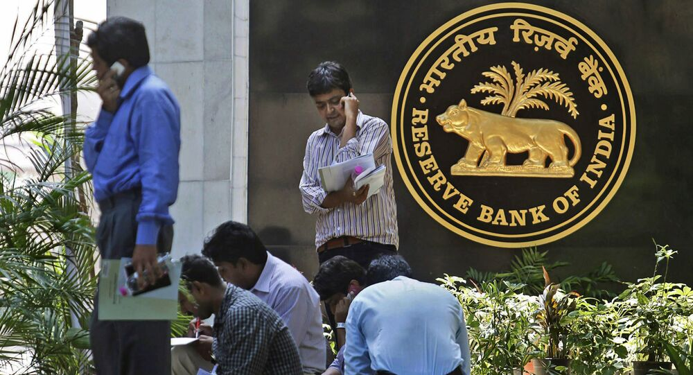Journalists wait next to the logo of the Reserve Bank of India (RBI), outside its head office in Mumbai, India, Tuesday, April 20, 2010