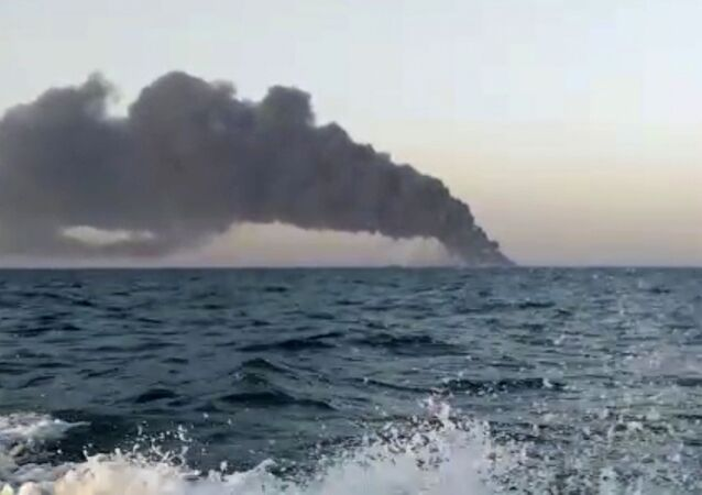 This image made from a video released on Wednesday, June 2, 2021 by Asriran.com, shows smoke rising from Iran's navy support ship Kharg in the Gulf of Oman