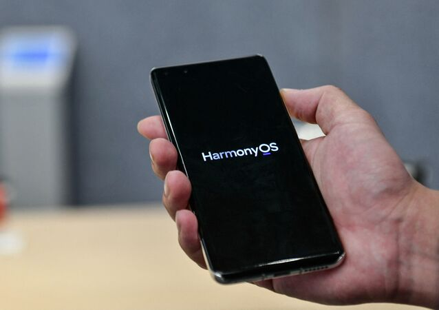 This photo taken on May 31, 2021 shows a staff member displaying a Huawei smartphone with the HarmonyOS operating system at the Huawei flagship store in Shenzhen, in China's southern Guangdong province.