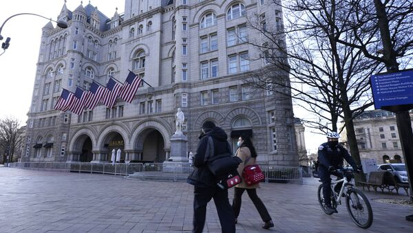 People walk by and a police officer rides a bicycle near The Trump International Hotel, Thursday, March 4, 2021, in Washington - Sputnik International