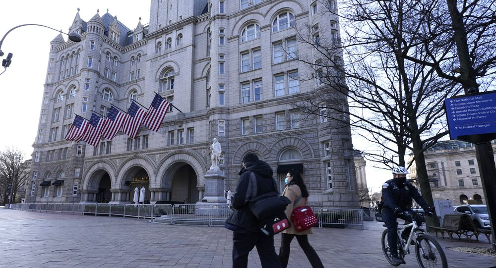 People walk by and a police officer rides a bicycle near The Trump International Hotel, Thursday, March 4, 2021, in Washington