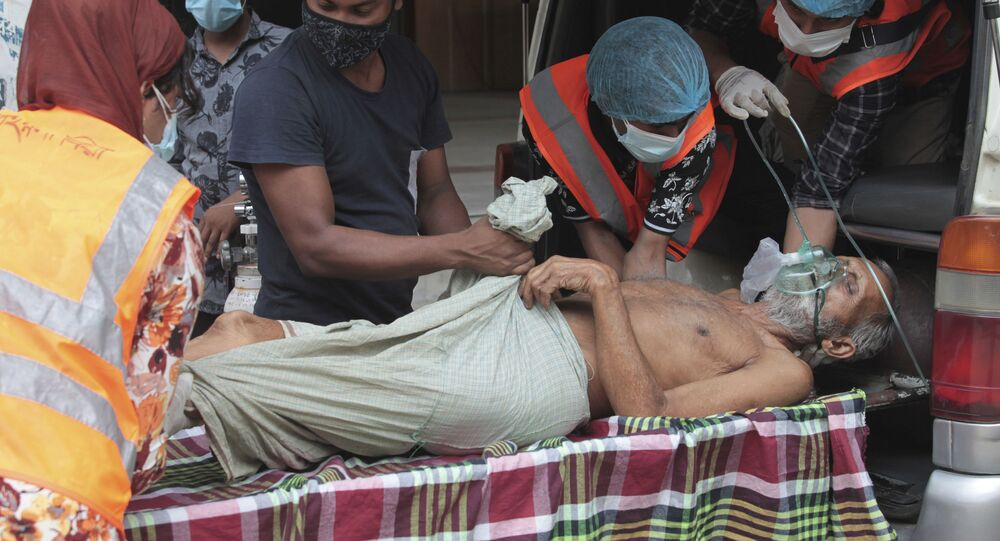 Paramedics and volunteers carry an elderly COVID-19 patient after he arrived at a hospital in Dhaka, Bangladesh, Friday, April 30, 2021