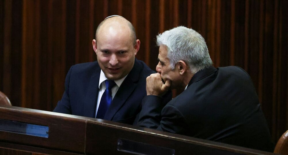 Yamina party leader Naftali Bennett smiles as he speaks to Yesh Atid party leader Yair Lapid, during a special session of the Knesset whereby Israeli lawmakers elect a new president, at the plenum in the Knesset, Israel's parliament, in Jerusalem June 2, 2021.