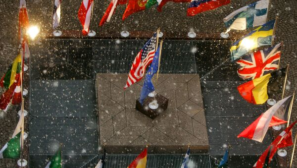 The flags of the United States and the European Union stand amid the national flags of the European Union nations during a gentle snowfall at European Union headquarters  in Brussels, Belgium, Tuesday, Feb. 22, 2005 - Sputnik International